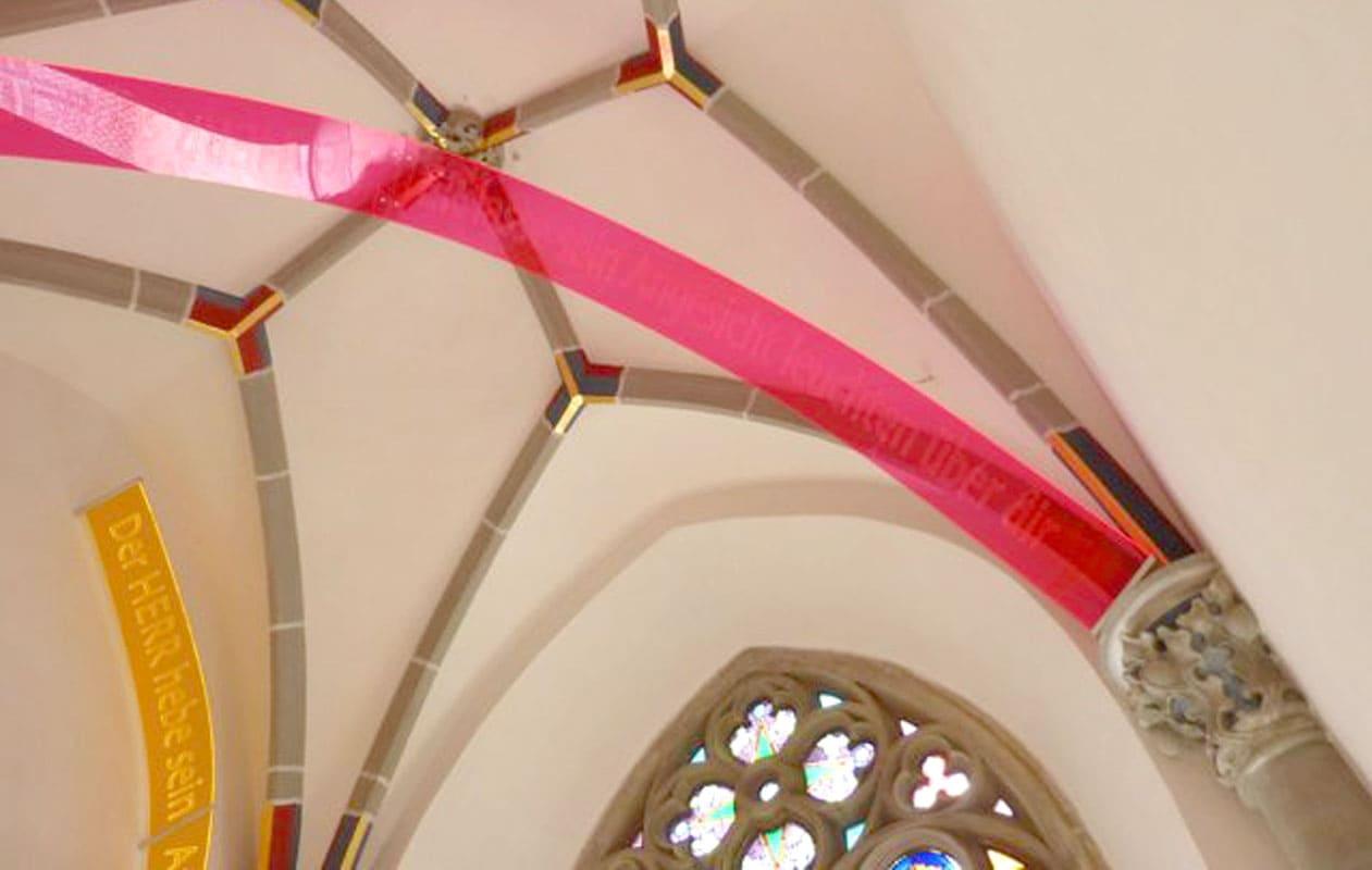 """Lasergravierte """"Schriftbögen"""" als Kunstinstallation in einer Kirche nach dem Entwurf von Sonja Weber."""
