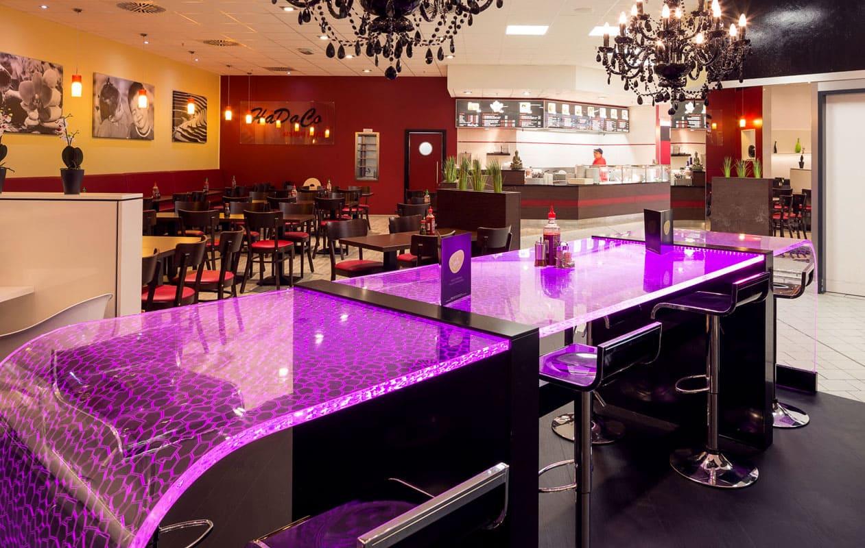 Das transparente Plexiglas® leitet über Gravurlinien farbiges LED-Licht vom Kopfende her durch die gesamte Länge des Tisches. Foto: BeMoss