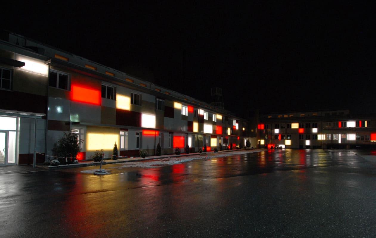 Witterungsbeständige Fassadenverkleidung aus transluzenten Lamilux Glasfaserpaneelen hinterleuchtet mit Lightpanel splash. Foto: axis